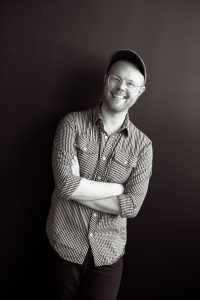 Photo of Scott standing with his arms crossed