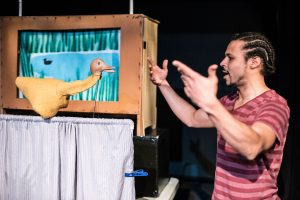A puppet artist interacts with a duck puppet