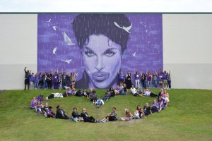 people sitting in the grass in front of a purple mural of the artist Prince